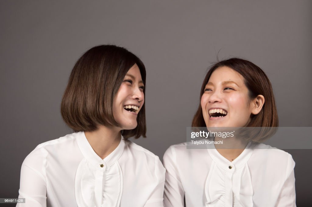 Twin sisters laughing loud : Stock Photo
