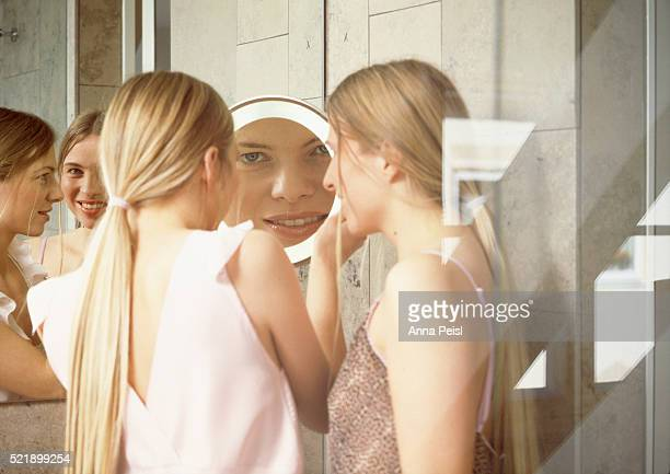 Twin sisters looking at themselves in the mirror