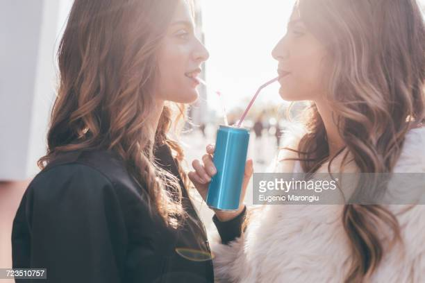 Twin sisters, outdoors, drinking can of soft drink with straws
