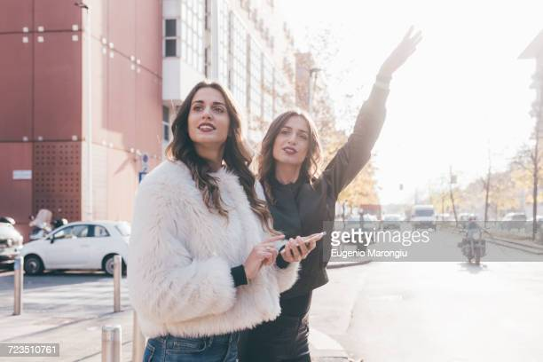 Twin sisters, outdoors, hailing taxi