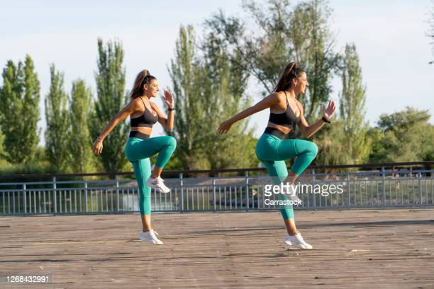 twin sisters perform sport at sunset in park. - kicking stock pictures, royalty-free photos & images