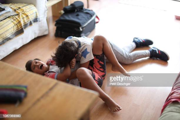 twin sisters playfully roughhousing at home. - mixed wrestling stock pictures, royalty-free photos & images