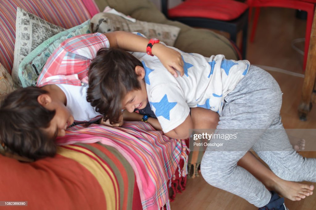 Twin sisters playfully roughhousing at home. : Stock Photo
