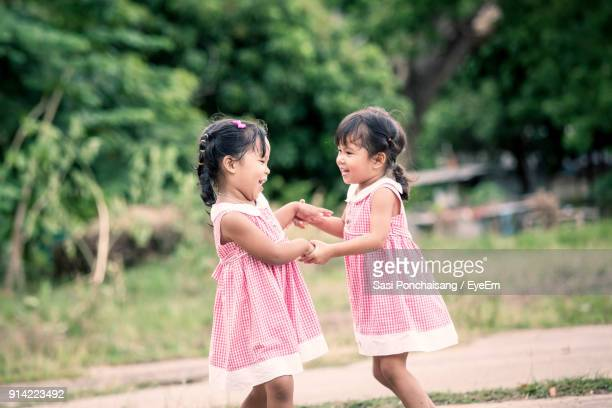 twin sisters playing at public park - very young thai girls fotografías e imágenes de stock