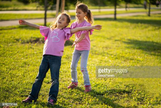 twin sisters playing in nature - trust stock pictures, royalty-free photos & images