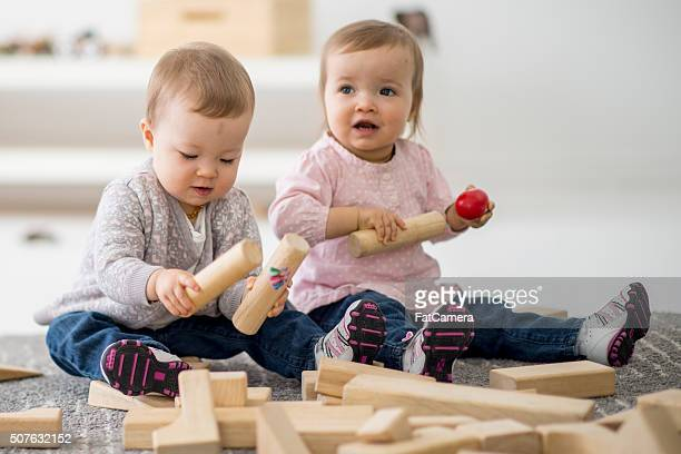 Twin sisters playing together in preschool.