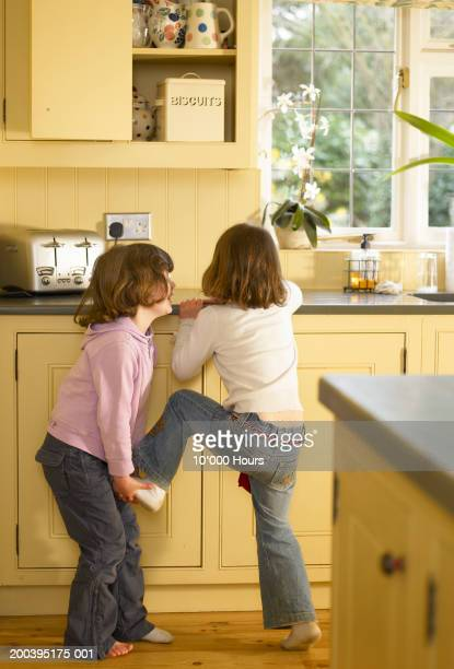 Twin sisters (5-7) reaching for biscuit tin in kitchen