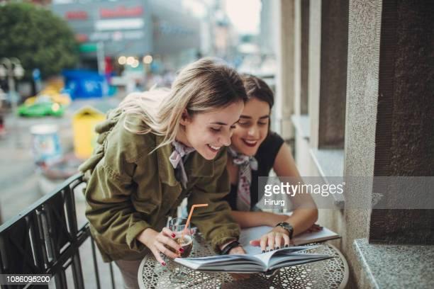 zwillingsschwestern lesen auf dem balkon - nur erwachsene fotos stock-fotos und bilder