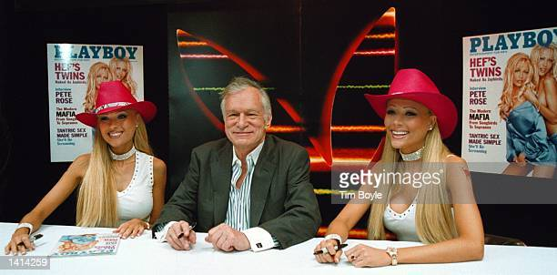 Twin sisters Sandy left and Mandy Bentley right along with Playboy''s Hugh Hefner center pose for a photograph before signing autographs at the Crown...