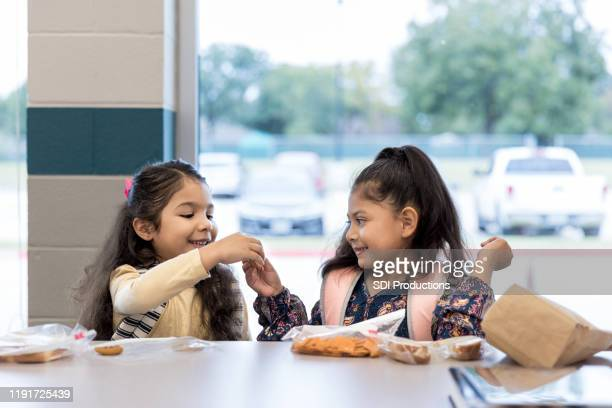 twin sisters share lunch in the school cafeteria - cracker snack stock pictures, royalty-free photos & images