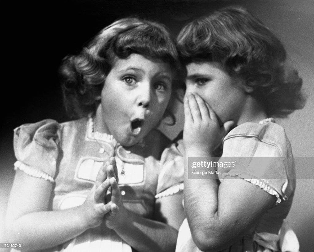 Twin sisters sharing secrets : News Photo