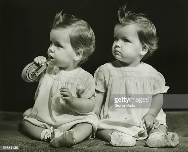 Twin sisters (9-12 months)sitting on blanket, (B&W), portrait
