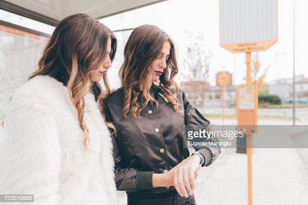 Twin sisters standing at bus shelter, looking at wristwatch