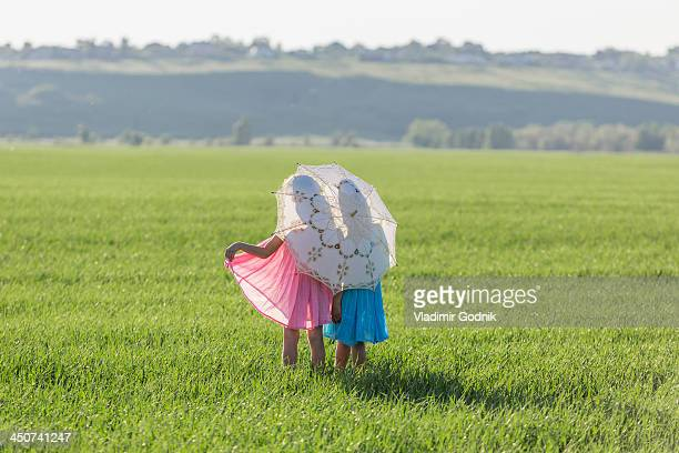 Twin sisters standing in a sunny field under an umbrella