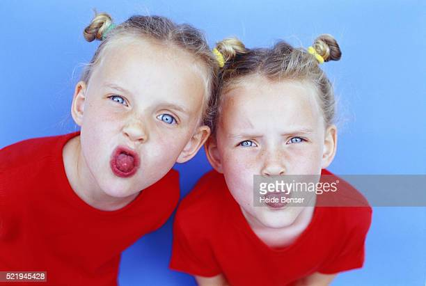 Twin sisters sticking out their tongues