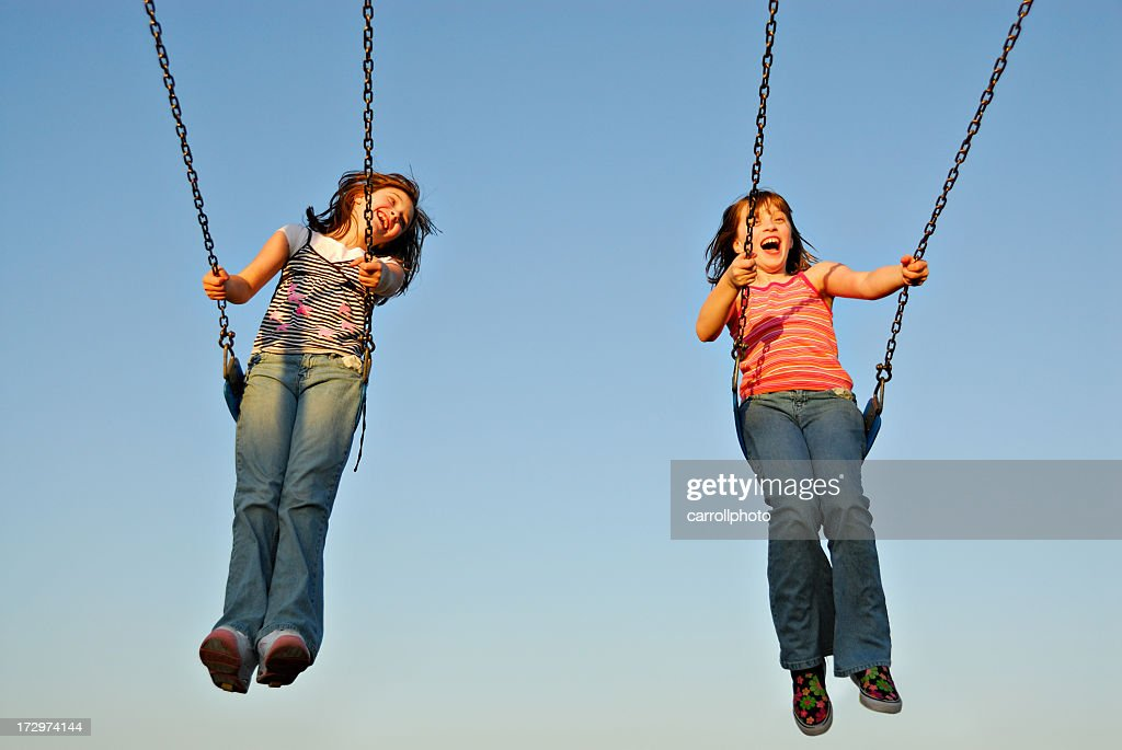 A twin sisters swinging happily on a sunny day : Stock Photo