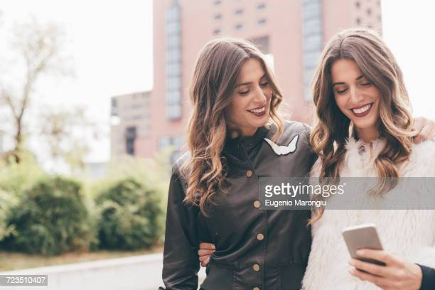 twin sisters, walking outdoors, looking at smartphone, smiling - identical twin stock pictures, royalty-free photos & images