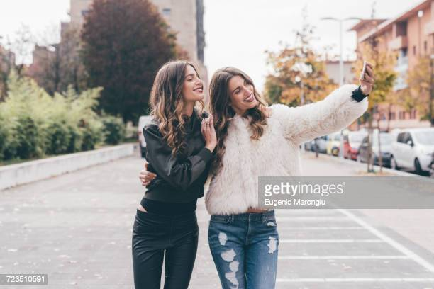 Twin sisters, walking outdoors, taking selfie using smartphone
