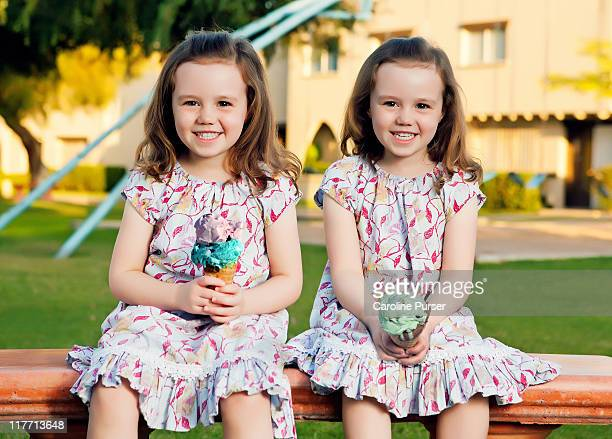Twin sisters with ice-cream on a park bench