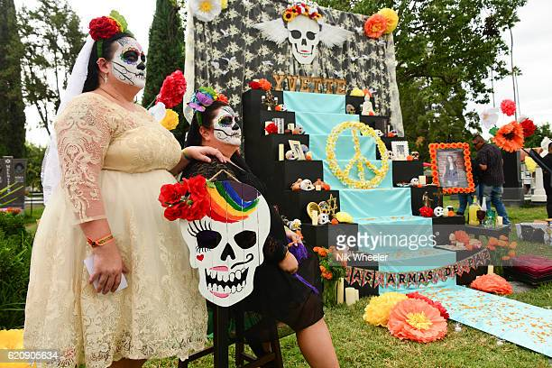twin sisters with painted faces at their family altar during day of the dead celebrations in hollywood cemetery, los angeles, california, usa - day of the dead festival stock photos and pictures