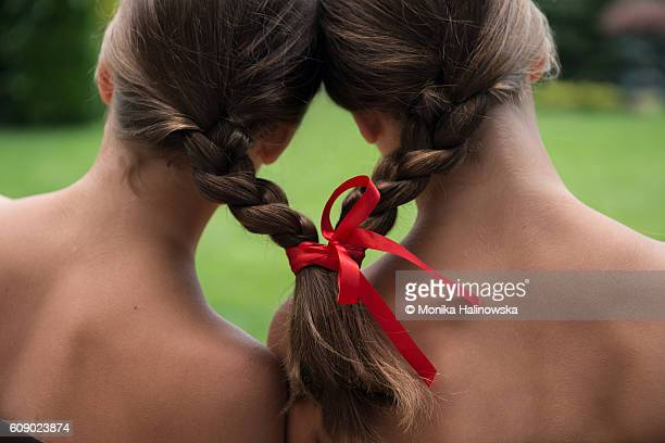Twin sisters with pigtails tied with a red ribbon