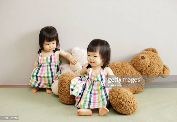 Twin sisters with teddy bear