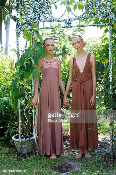 twin teenage girl (13-14) standing in garden - blasius erlinger stock pictures, royalty-free photos & images