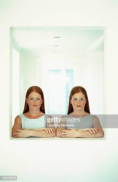Twin teenage girls (17-19) indoors, portrait