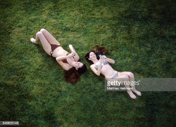 Twin Teenage Girls Using Cell Phones on Lawn