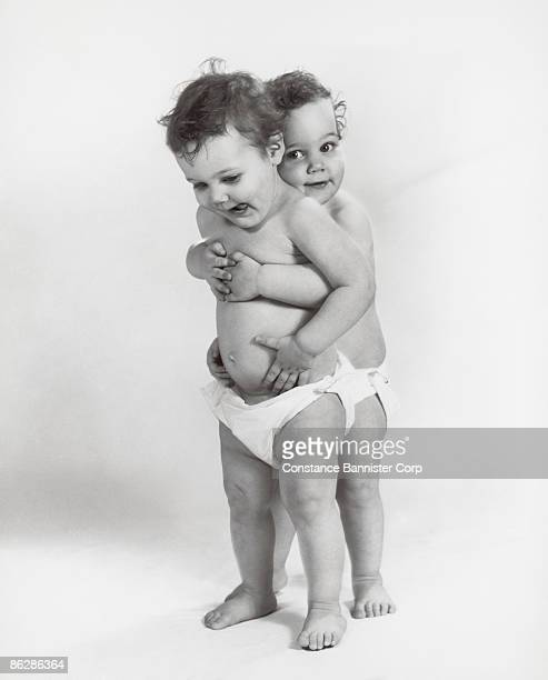 twin toddlers hugging - constance bannister stock photos and pictures