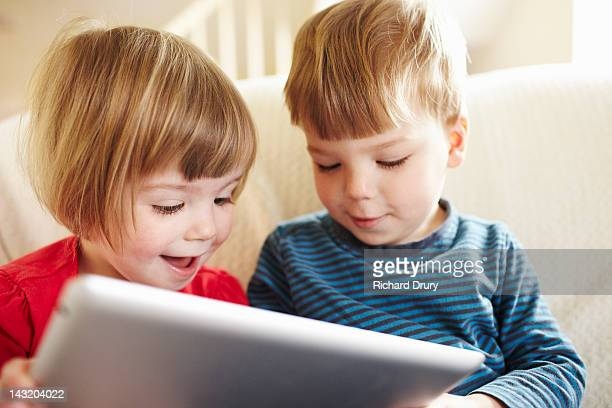 twin toddlers using digital tablet - richard drury stock pictures, royalty-free photos & images
