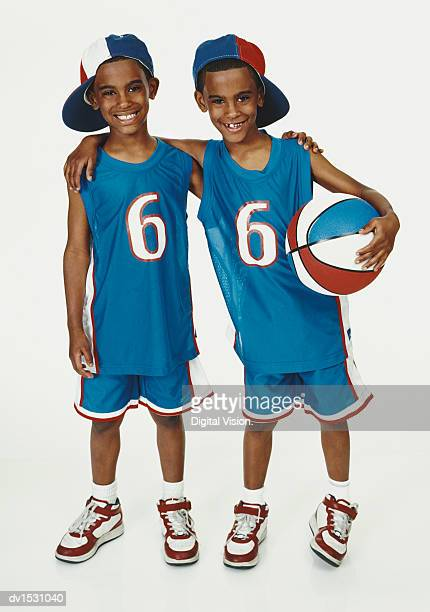 twinboys stand side-by-side in blue sports strips and holding a basketball - blue shorts stock pictures, royalty-free photos & images