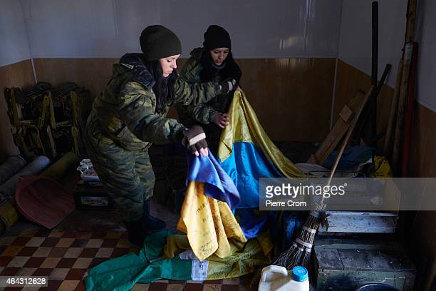 Twins Anya and Katya both 19 years and have been with the DPR army since October 2014 look at Ukrainian flags seized in Debaltseve in a base on the...