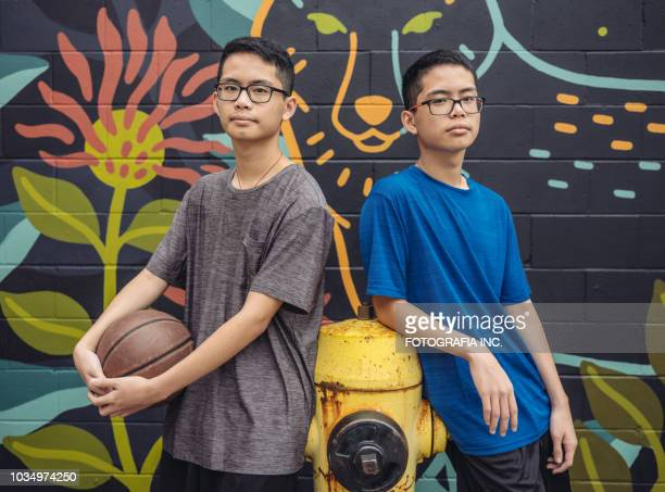 twins at basketball - asian twins stock photos and pictures
