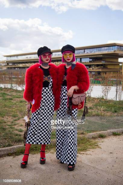 Twins Aya Amiaya and Ami Amiaya wearing black and white checked skirt and red fur coat is seen before the Christian Dior show on September 24 2018 in...