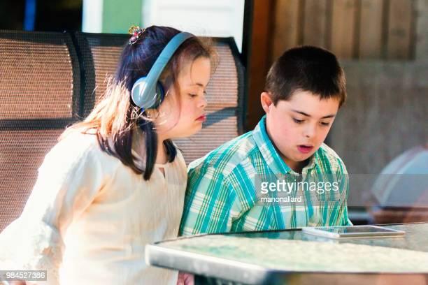 gemelos de hermano y hermana de 12 años con autismo y síndrome de down en la vida cotidiana - autismo fotografías e imágenes de stock