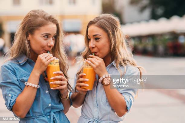 Twins drinking juice outdoors