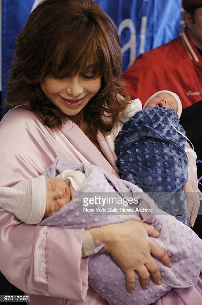 Twins Francesca and Gian snooze through their first news conference in the arms of their smiling mother Aleta St James on the day after the babies...