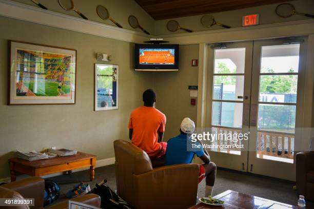 Twins Francis Tiafoe, L, and Franklin Tiafoe study television tennis matches after the rains stopped their outdoor games at the Junior Tennis...