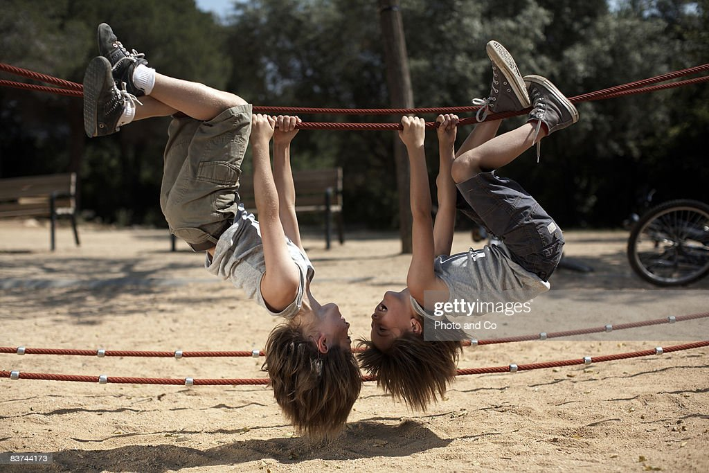 twins hang from structure in park : Stock Photo