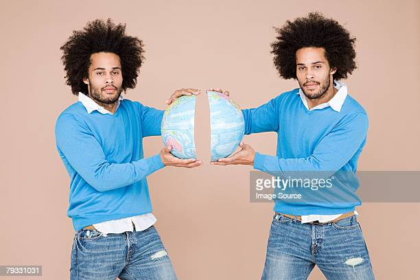twins holding two halves of the earth - identical twin stock pictures, royalty-free photos & images