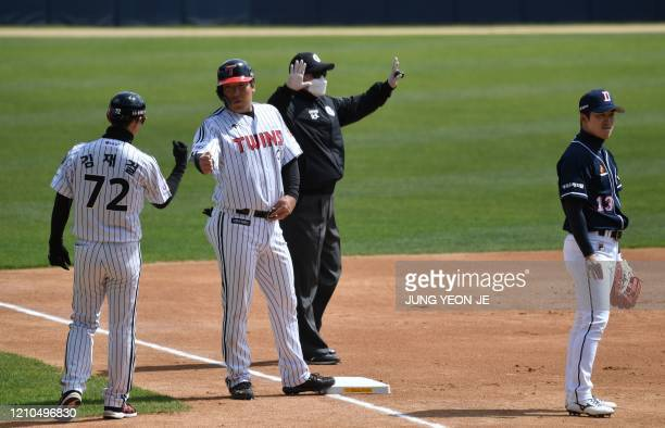 LG Twins' Kim Hyunsoo reacts after stealing the third base as a referee wearing a face mask gestures during a preseason baseball game between...