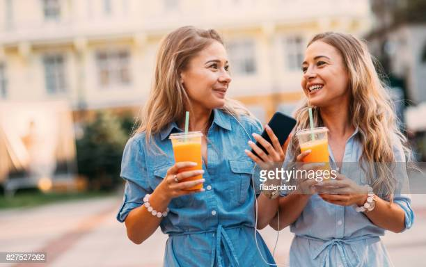 Twins listening to music and drinking juice outdoors