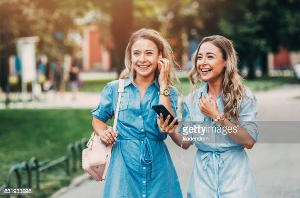 Twins listening to music outdoors