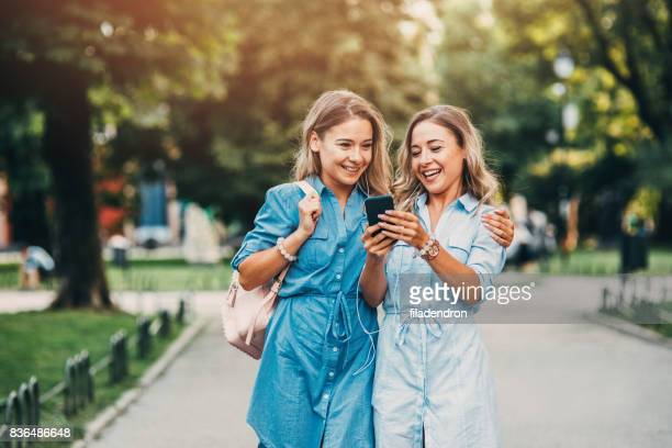 twins listening to music outdoors - arm around stock pictures, royalty-free photos & images