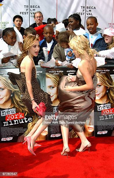 Twins MaryKate and Ashley Olsen hang onto their skirts against a fresh gust of wind while signing autographs before a screening of the movie New York...