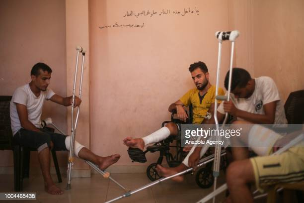 Twins Muhammed and Ahmed Diyab Said and Bilal Diyab are seen with crutches and a wheelchair after Israeli forces opened fire on them and...