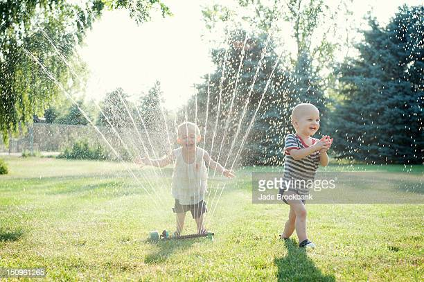 Twins playing in sprinkler