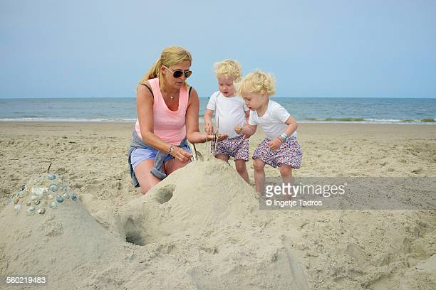 Twins playing on beach with their grandmother