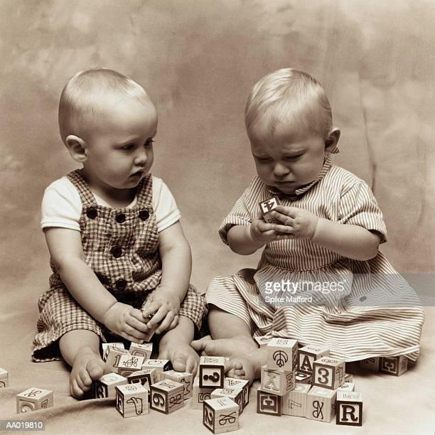 Twins Playing with Alphabet Blocks